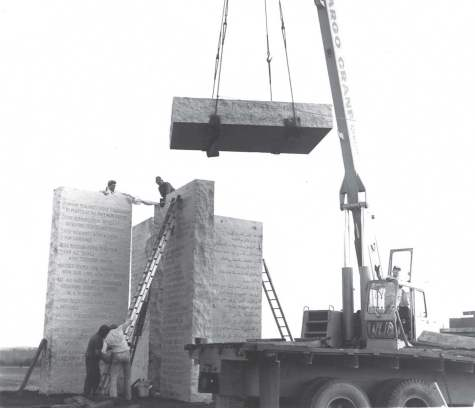 Workers carefully position the capstone onto the vertical pillars of the Georgia Guidestones. Drilled through the capstone is a slot enabling the daily noontime sun to illuminate the day of the year etched into one of the pillars. (Photo provided)
