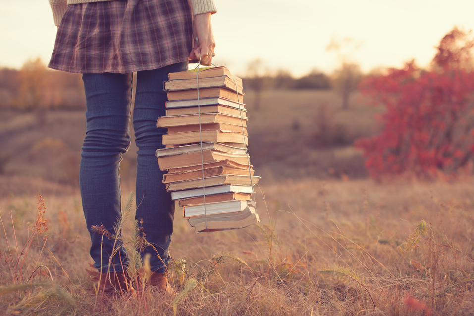 woman in field holding books