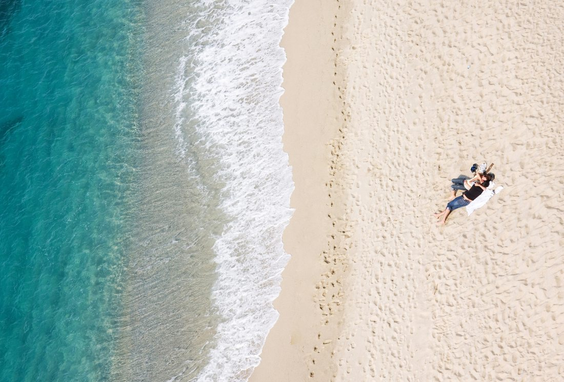 View of young couple resting on tropical beach, lots of copyspac