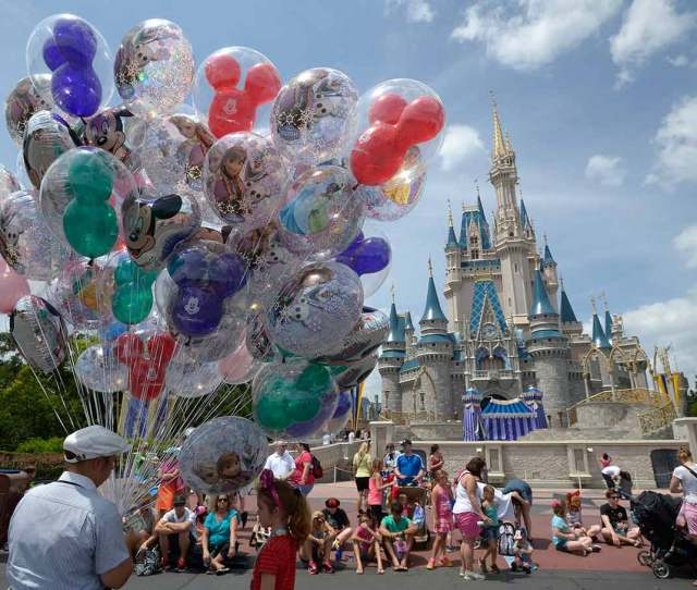 A Cast Member Sells Balloons In Front Of Cinderella Castle At Walt Disney Worlds Magic Kingdom Theme Park In Lake Buena Vista Florida On May 10 2014