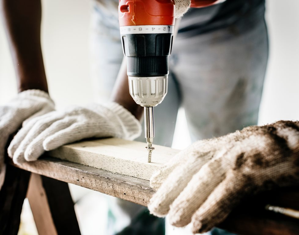 using a drill to fix an item on the home