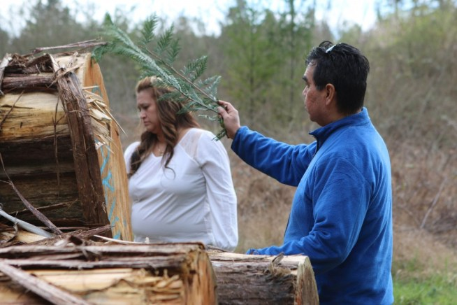 Sherry McCarthy, VIUSU Chairperson, and Qwaya Sam, a member of Ahousaht First Nation and one of the carvers in the totem pole project, take part in the blessing ceremony for two cedar trees donated by Western Forest Products. Photo by Shari Bishop Bowes