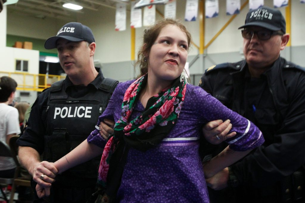 Woman wearing bright clothing sneers as police restrain her arms and guide her out of crowd.
