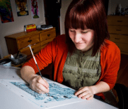 A woman with red dyed hair works on a comic with blue ink. She is wearing a red sweater, a green shirt, and is smiling at the comic.