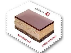 """A controversial interpretation of a Nanaimo Bar is displayed on a Canada Post stamp. Well the top layer is an accurate depiction, the middle layer is much thicker than an average Nanaimo Bar, and the bottom layer is almost non-existent. """"Nanaimo Bar"""" accompanies the image in French and English."""
