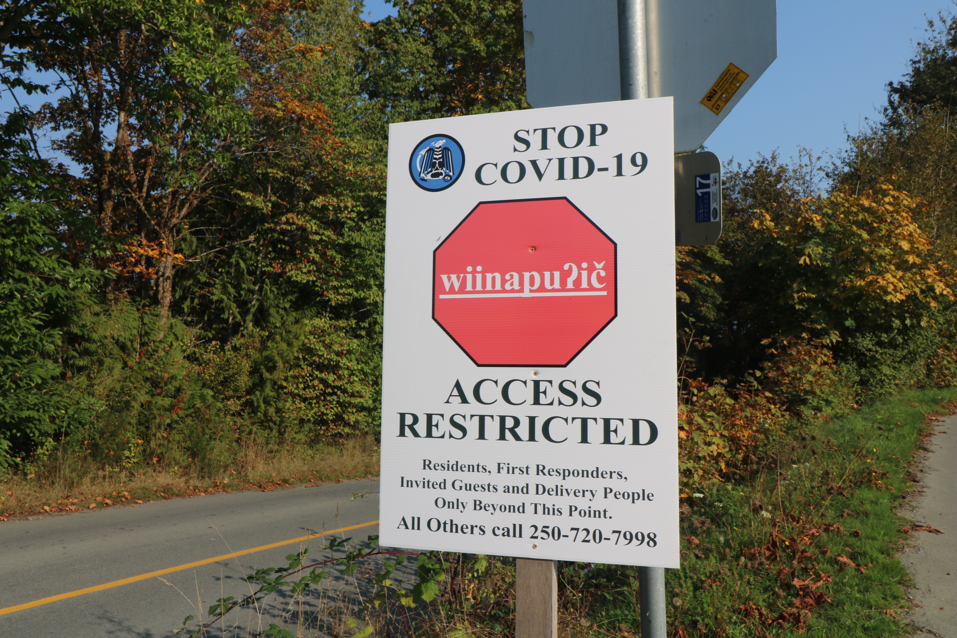 """White sign on the Tseshaht First Nation Reserve that reads """"STOP COVID-19 access restricted. Residents, first responders, invited guests and delivery people only beyond this point"""""""