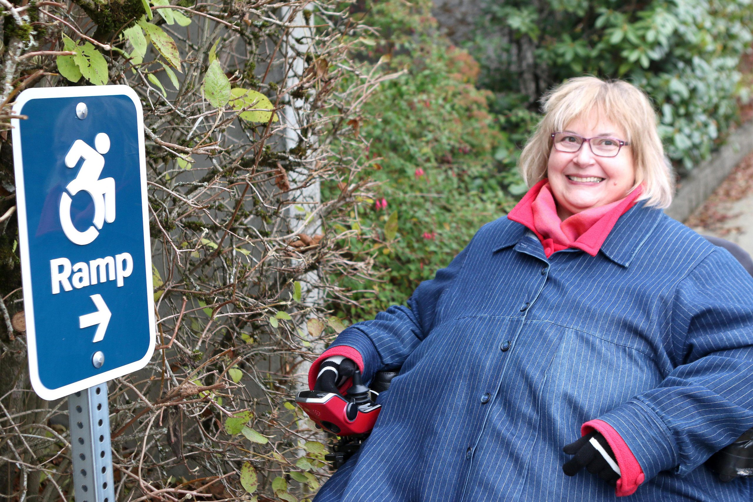 """A lady sits in a wheelchair smiling by one of the new wheelchair route signs that reads """"ramp"""" pointing to the direction of the ramp."""