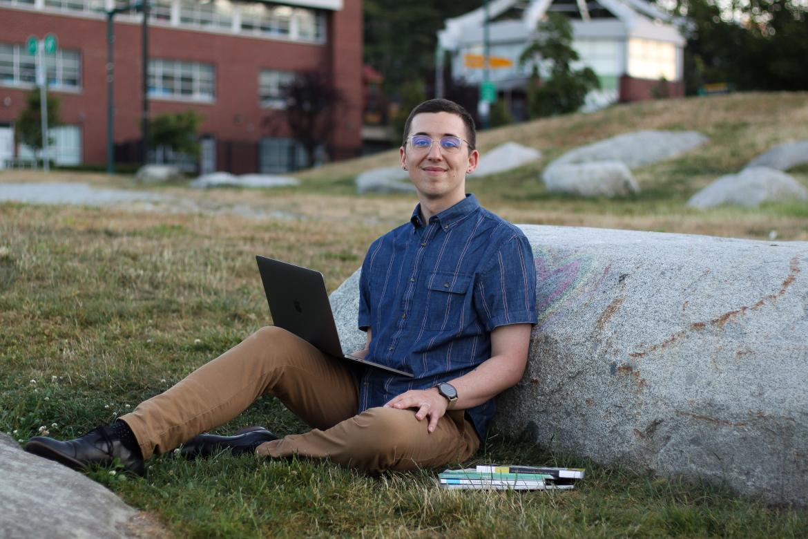 Spenser Smith sits against a rock with his laptop on his lap.