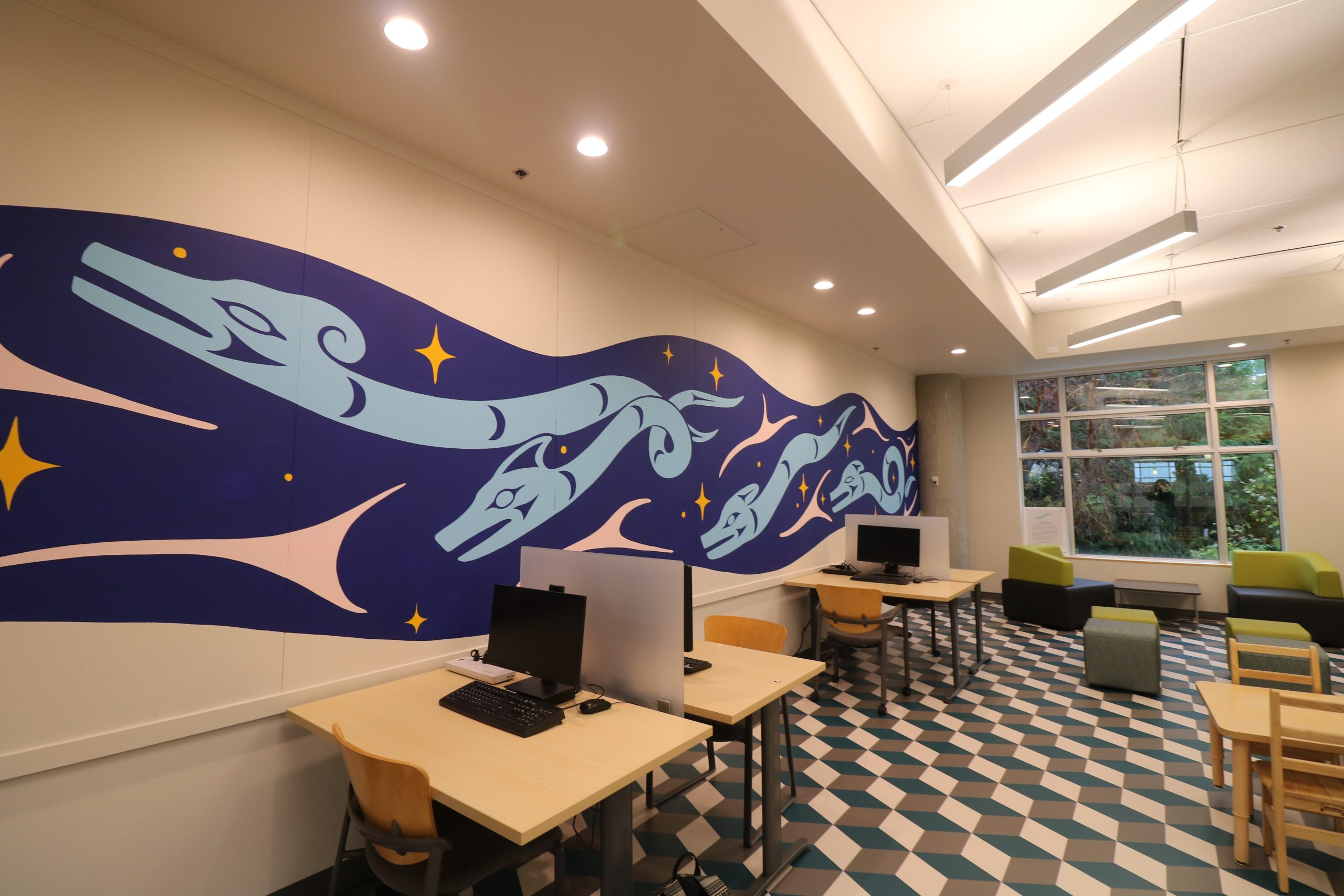 The image shows Eliot White-Hill's mural 'Lhuxw (To Flow)' that stretches across the whole wall of the family room