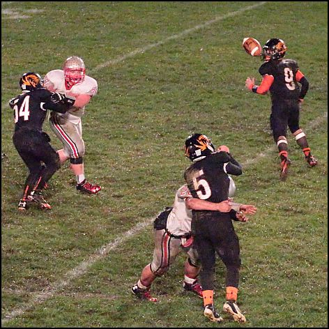 Lane (#5) manages to get the pass off for a completion while being hit.