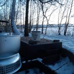 Little fireplace outise on the snow with coffee mug