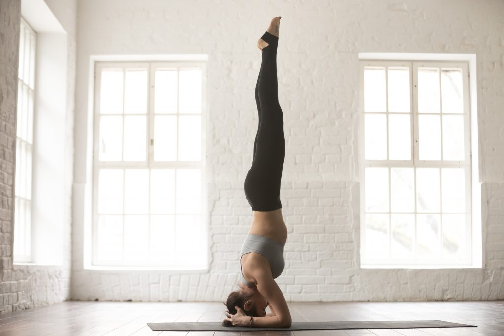 Young attractive yogi woman practicing yoga concept, standing in salamba sirsasana exercise, headstand pose, working out, wearing sportswear, full length, white loft studio background