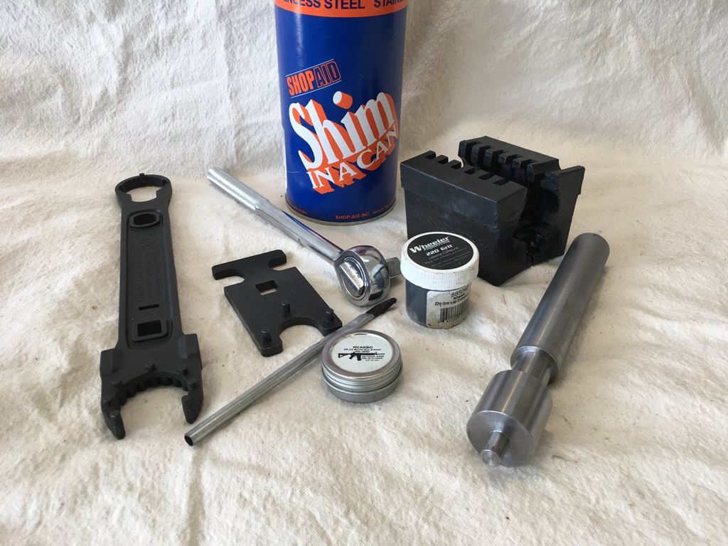 "Barrel assembly tools: nut wrench, action block, 0.001"" stainless steel shim stock, receiver face lapping tool, 220 grit lapping compound, aeroshell grease and brush"