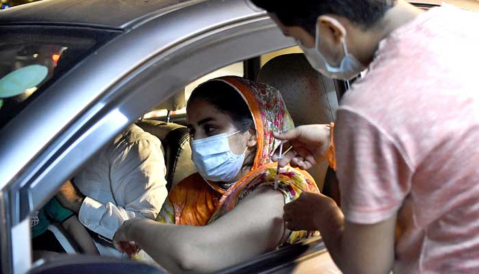 A woman being injected COVID-19 vaccine at a drive-through vaccination center setup at the Gaddafi Stadium in Lahore. Photo: APP