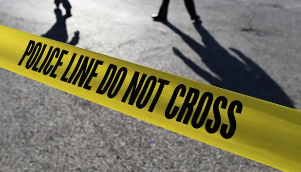 Police officers stand behind crime scene tape. — AFP/File