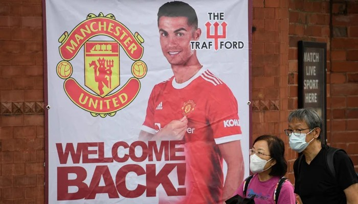 Fans walk past a banner featuring Manchester United´s new signing Cristiano Ronaldo at Old Trafford stadium in Manchester, northwest England on September 10, 2021. — AFP