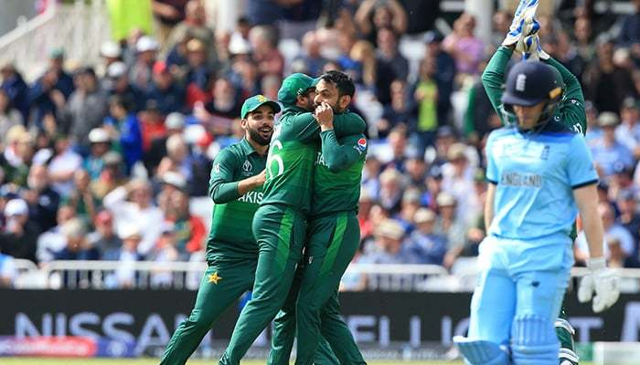 Mohammad Hafeez (3rd L) celebrates with teammates after taking the wicket of Englands Eoin Morgan. — AFP/File