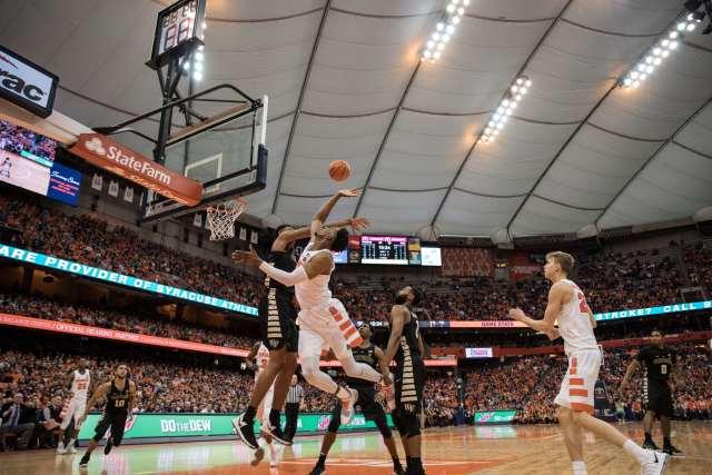 Oshae Brissett leaps toward the ball under the hoop off of a rebound.