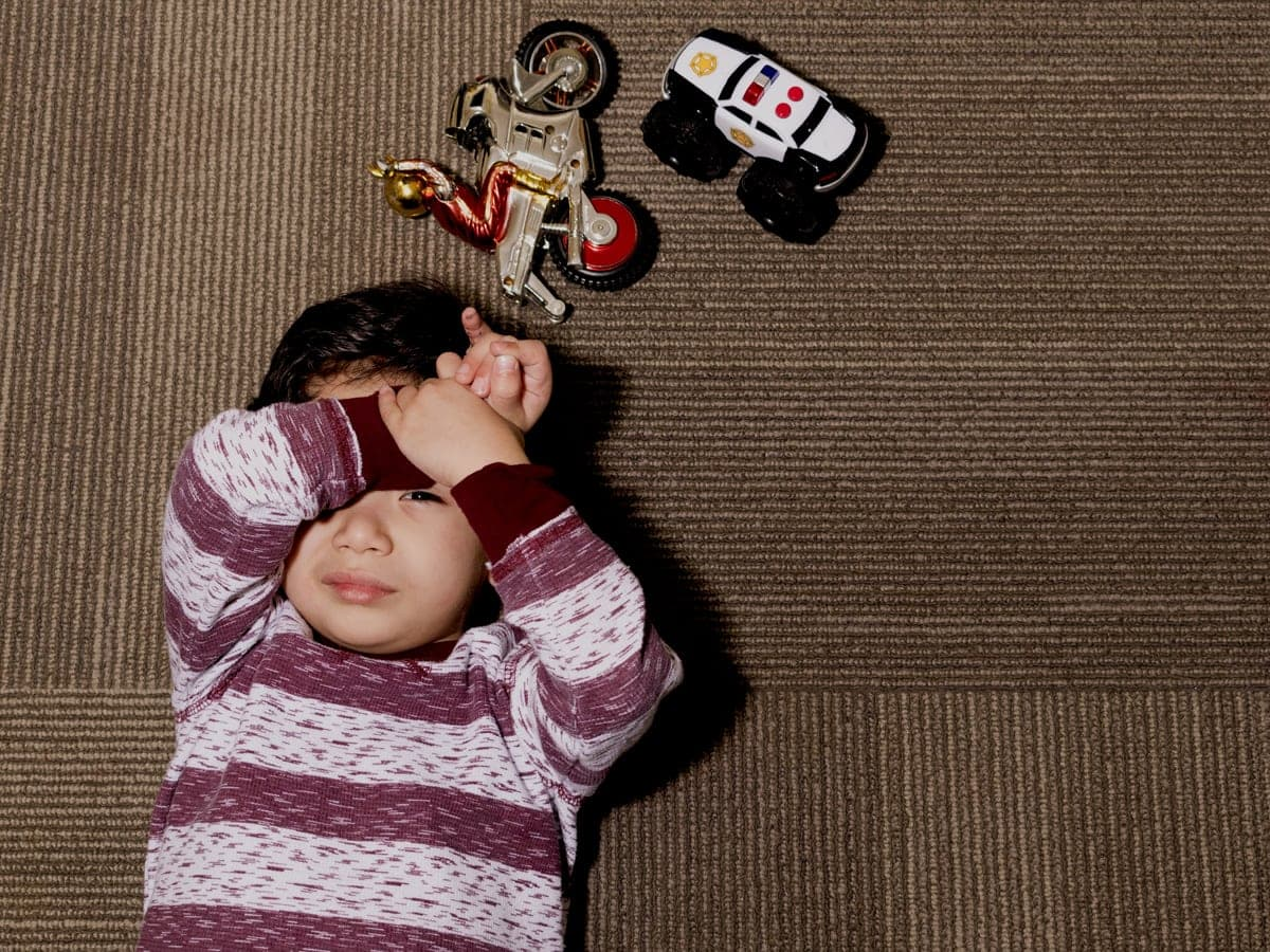 Young girl laying on floor with toys.