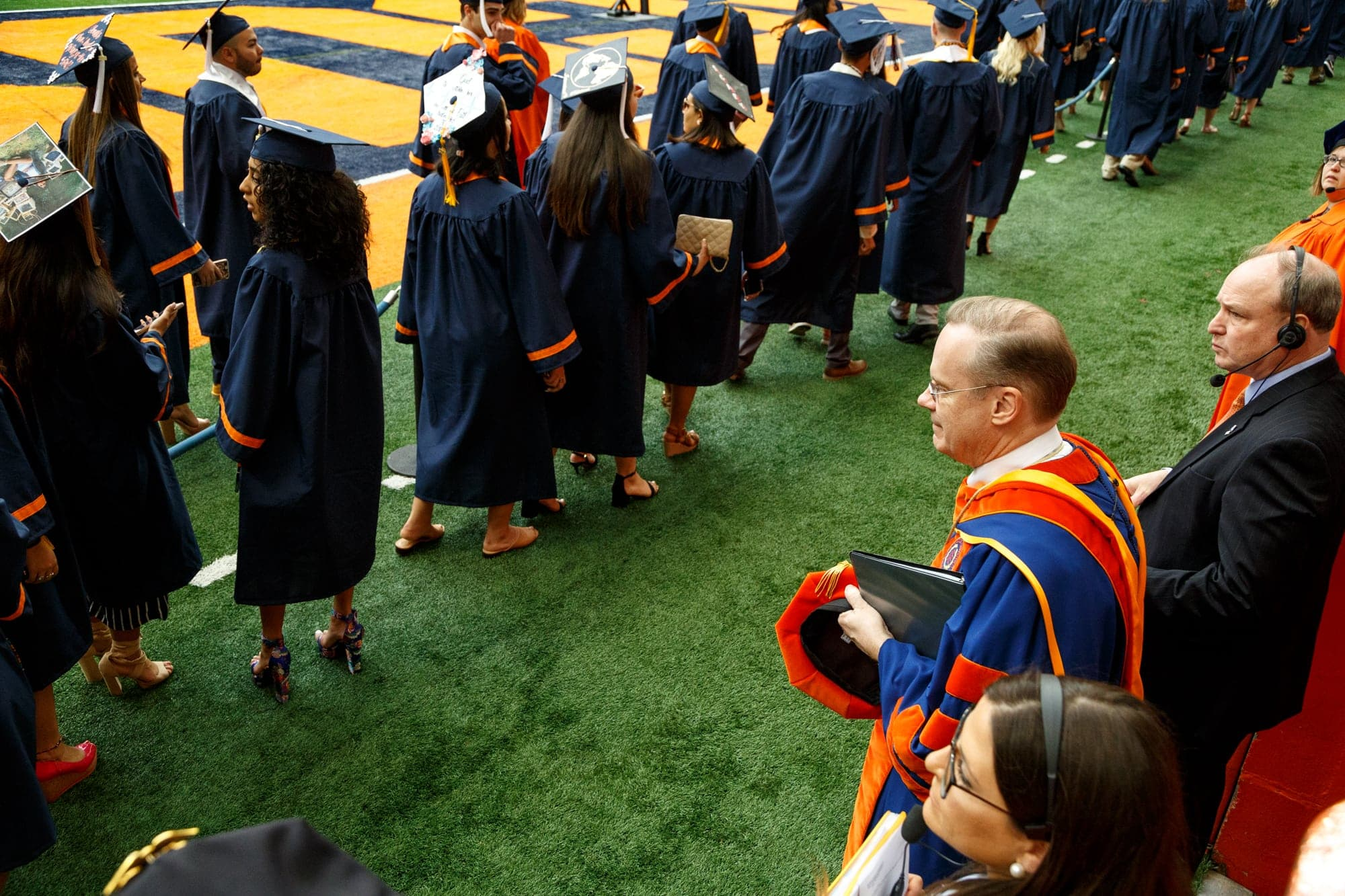 The Chancellor watches as students walk at commencement