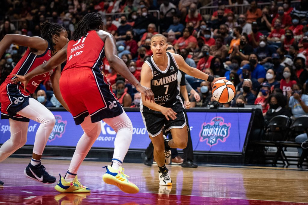 Minnesota Lynx guard Layshia Clarendon (7) drives into a double-team set by Tina Charles (31) and Ariel Atkins (7) during a game against the Washington Mystics (Photo credit: Domenic Allegra)