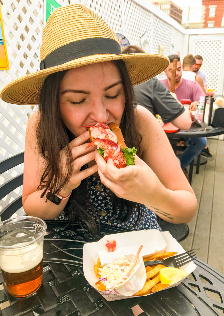 woman eating lobster roll and beach bar