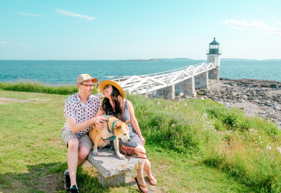couple with dog in front of light house