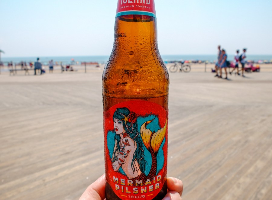 holding beer bottle with beach in background