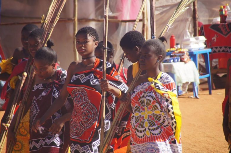 Swazi maidens carry reeds to present to the Queen Mother as tribute labor.