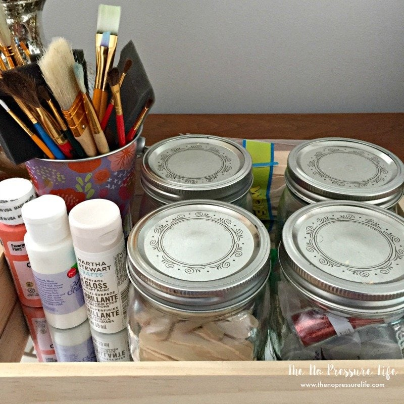 DIY art caddy with a tray and mason jars to organize art and craft supplies.