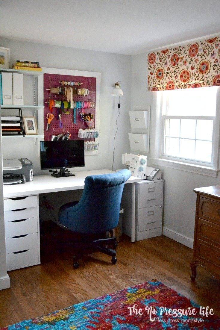 pretty craft room with white desk and pink peg board