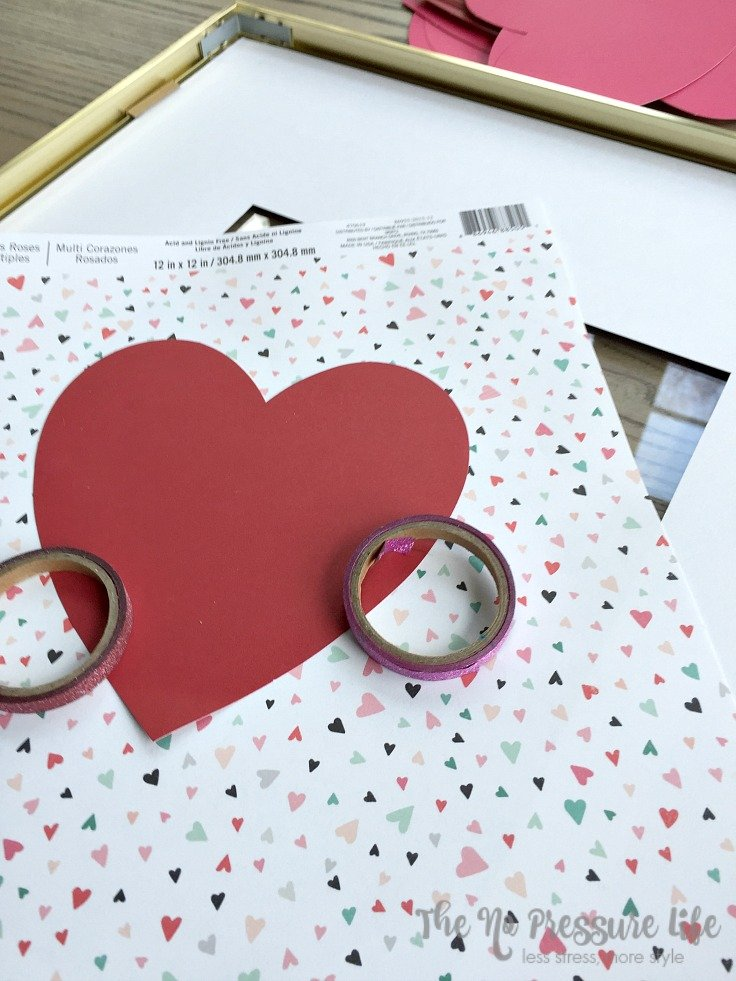 DIY Valentine's Day mantel decorations - scrapbook paper and washi tape on a wood table