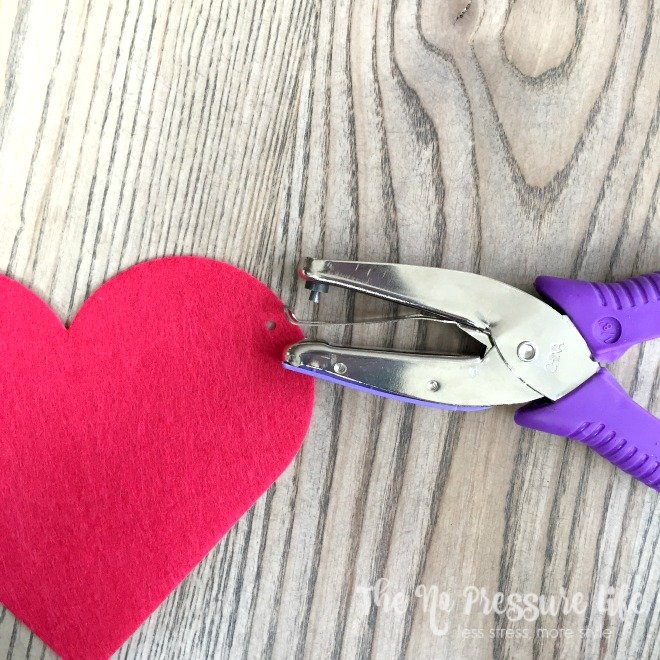 How to make Valentine's Day mantel decorations - Red felt heart and hold punch on a wood table