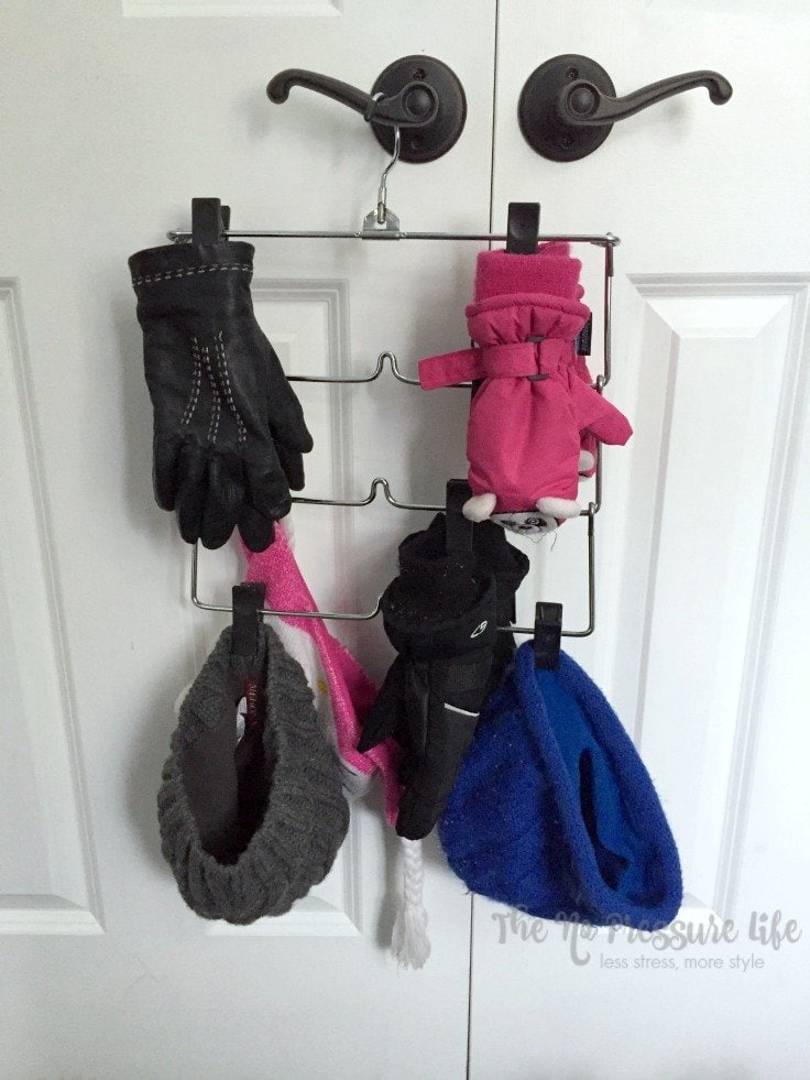 mittens, gloves and hats hanging to dry on a multi-tier skirt hanger