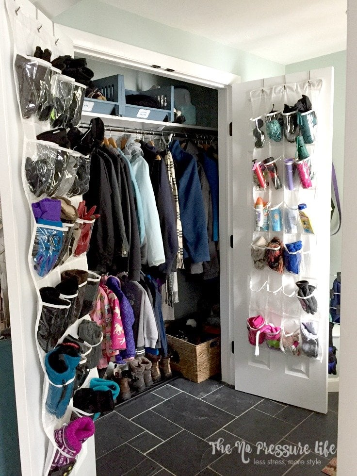Organized coat closet with double doors in a mudroom with slate floors