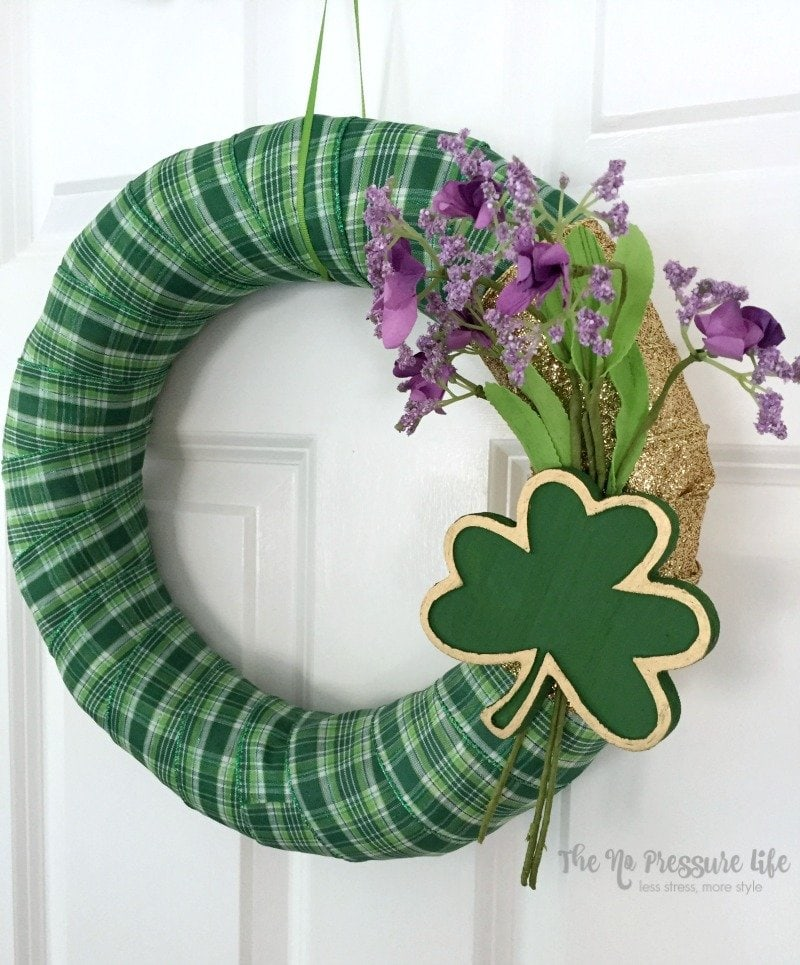 DIY St. Patrick's Day wreath with green plaid ribbon and a wood shamrock on a door