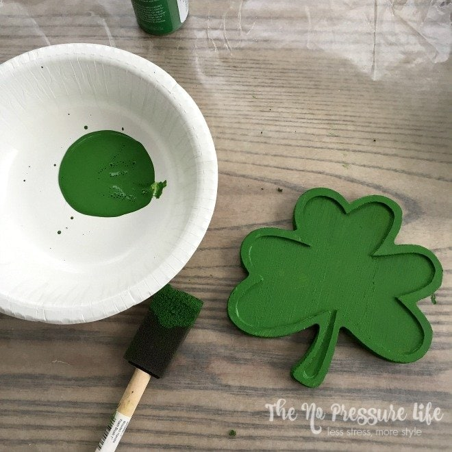 Painting a wood shamrock green for a DIY St. Patrick's Day wreath