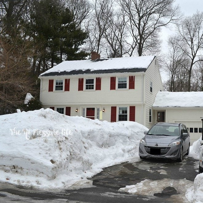 garrison colonial house in winter with several feet of snow