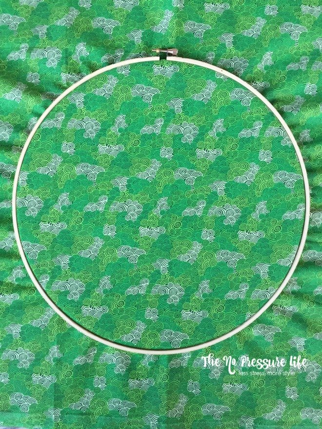 green fabric in an embroidery hoop for shamrock craft