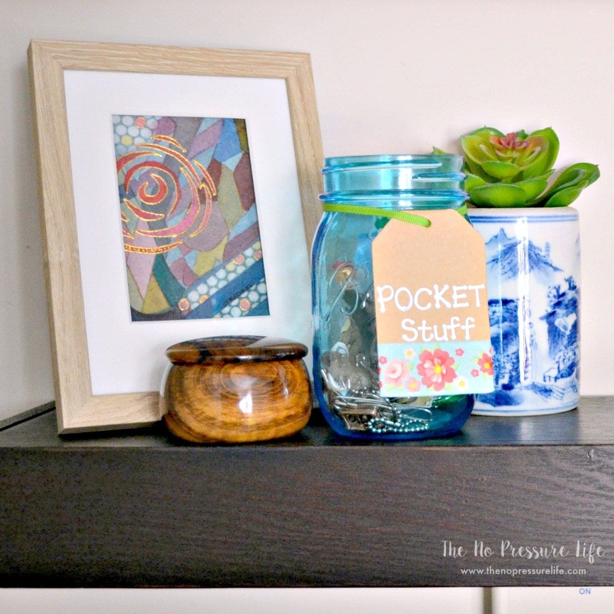 Simple laundry room shelf decor. See more of this small laundry room makeover at The No Pressure Life.
