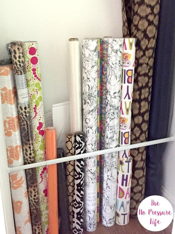 DIY Wrapping paper storage ideas: How to organize wrapping paper and gift wrap in a closet with a tension rod.