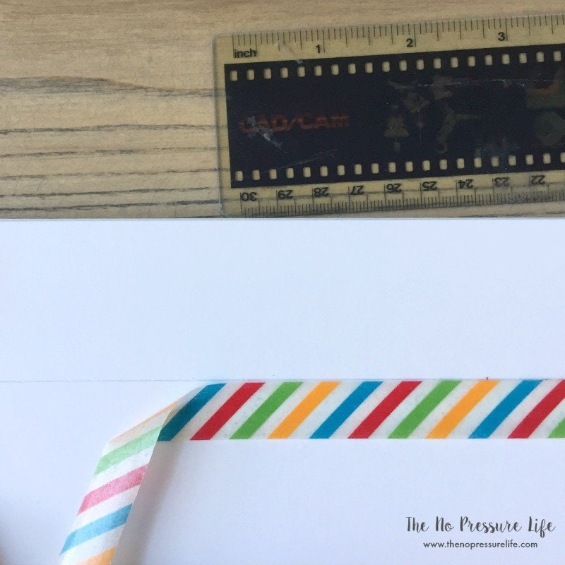 Ruler, white poster board and striped washi tape on a wood table