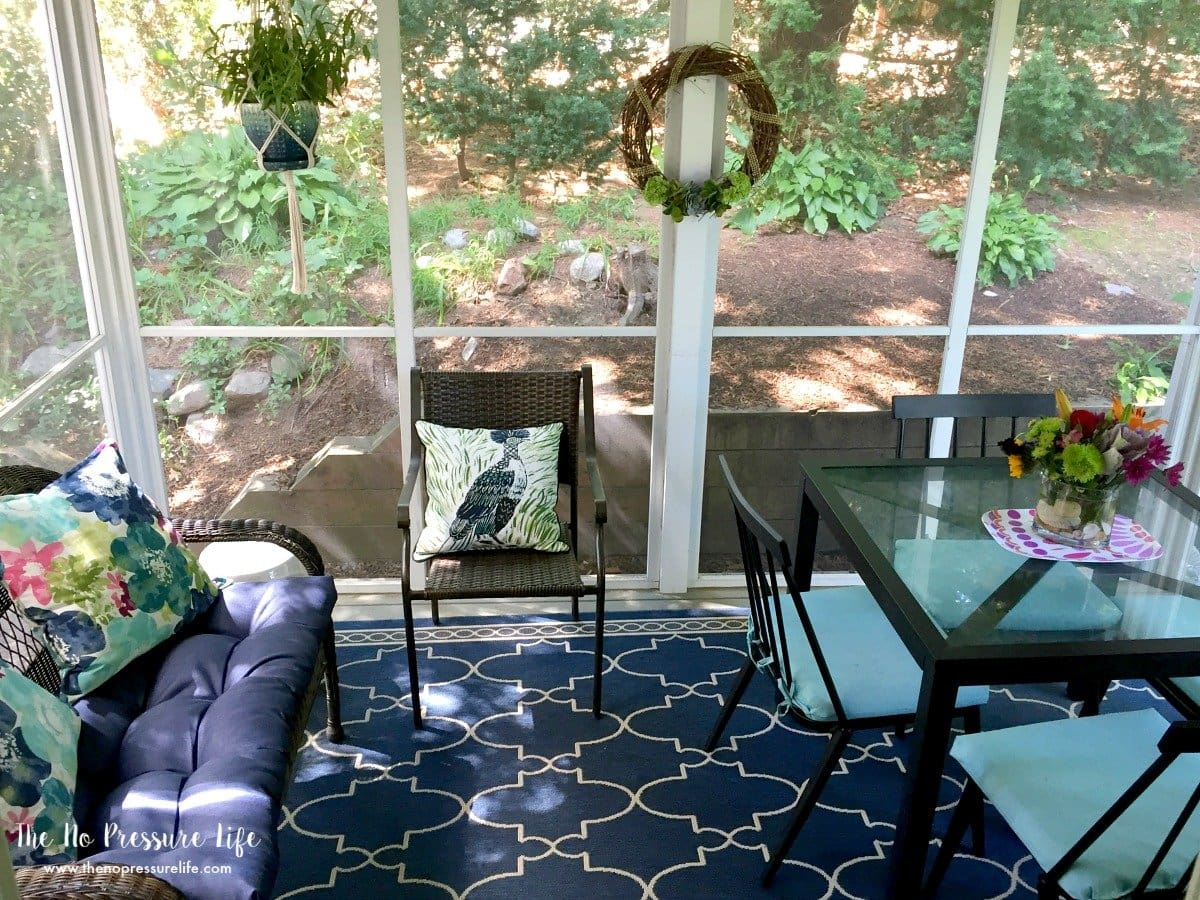 Bold blue rug in small screened-in porch
