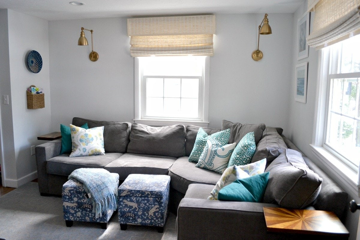 family room with gray sectional and brass wall sconces