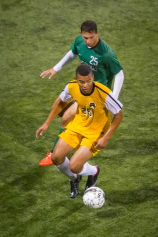 NKU soccer player Kobie Qualah dribble away from Marshal's Cory Shimensky in the first half of NKU's 2-1 loss against the Thundering Herd. NKU lost 2-1 to Marshall University Wednesday, Oct. 15, 2014 at NKU Soccer Stadium.