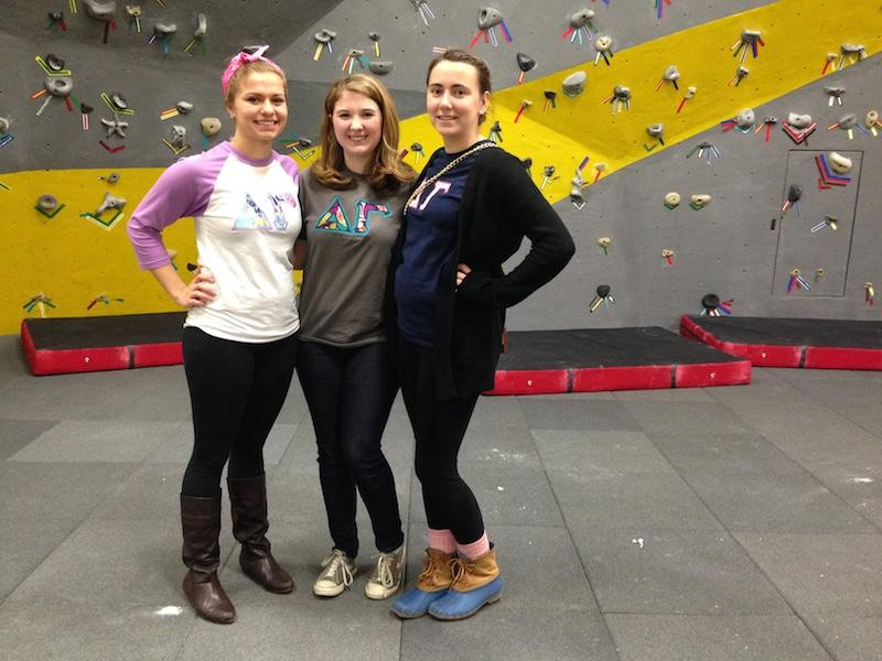 Alli Zembrodt(left) and her friends gather their strength to climb the rock wall, part of the homecoming festival.