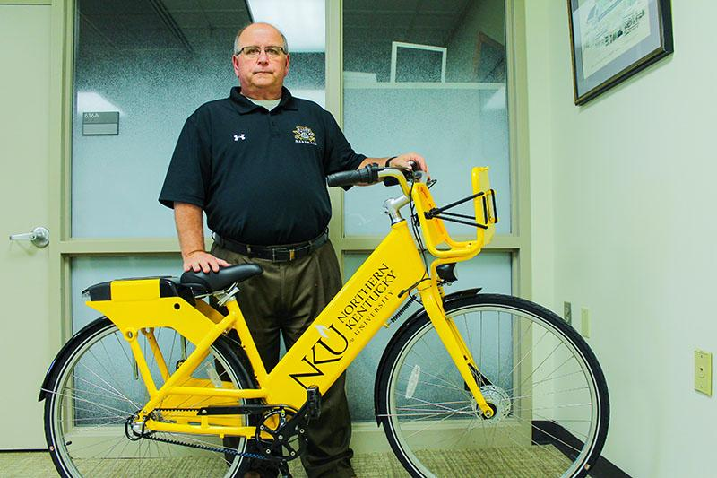 Andy Meeks, director of business operations and auxiliary services, poses with one of the new bikes. Meeks is partially responsible for bringing a bike share to campus.