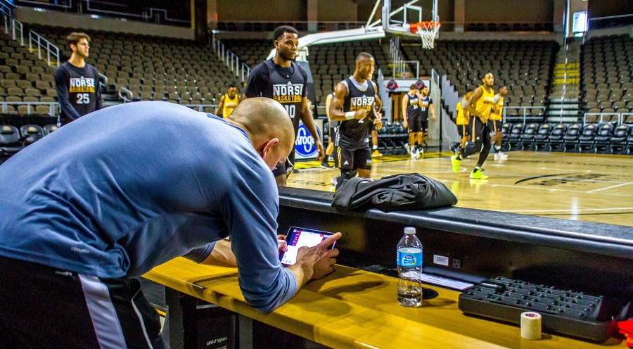 Brian+Boos+looks+over+the+data+from+the+Polar+Pro+on+an+iPad+while+the+men%27s+basketball+team+warm-ups+for+practice