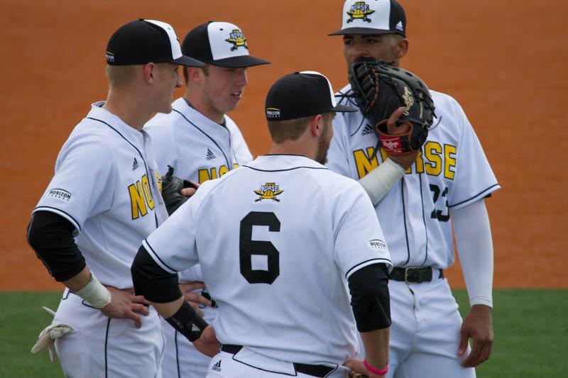 The Norse infield talks things over during a pitching change