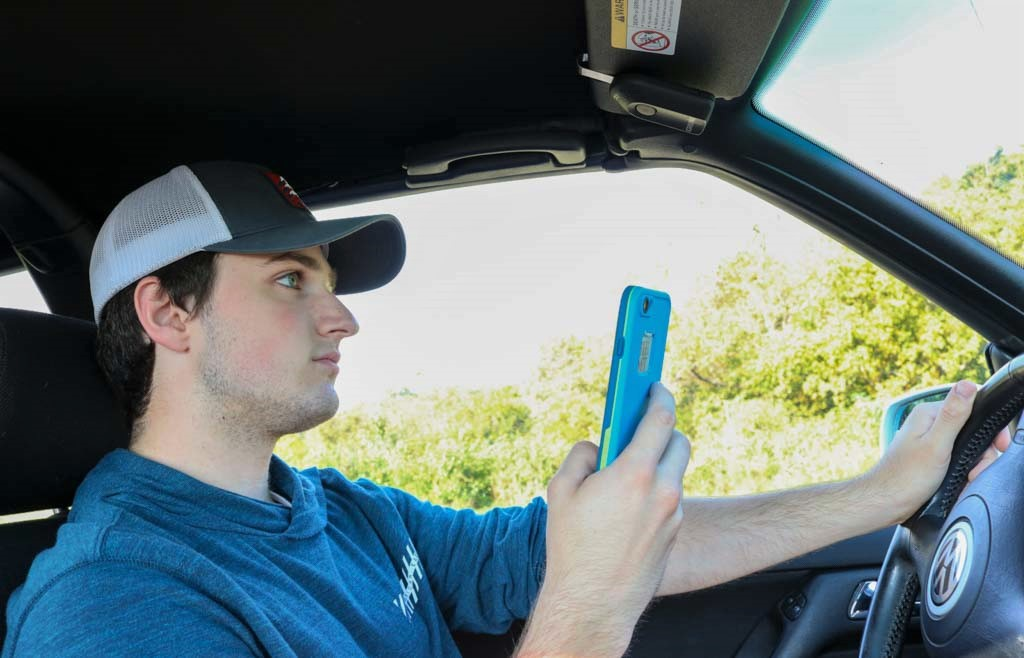Young adults often split their attention between their phone and the road, creating potentially dangerous situations